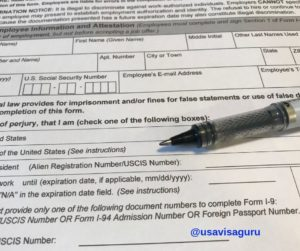 A close up photo of the I-9 form, along with a pen.